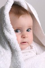 cute baby in a white towel after bathing