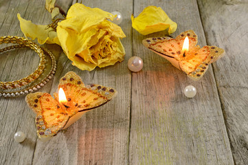 Yellow rose and butterfly candles with copy space