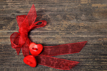 Two hearts tied red ribbon