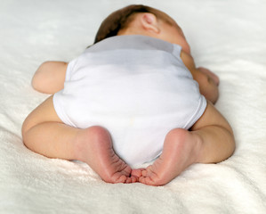 newborn baby sleeping on white.  adorable crossed legs and feet