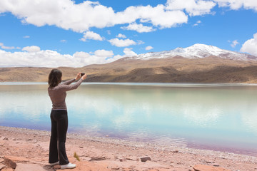 Woman taking pictures of lagoon Celeste, Bolivia