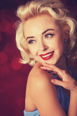 Pretty blond girl model like Marilyn Monroe on red background