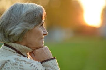 thinking senior woman in autumn park
