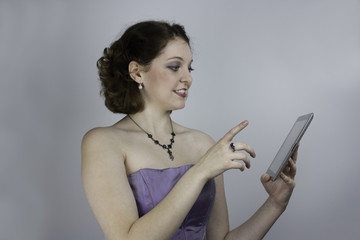 Young woman wearing purple gown uses tablet