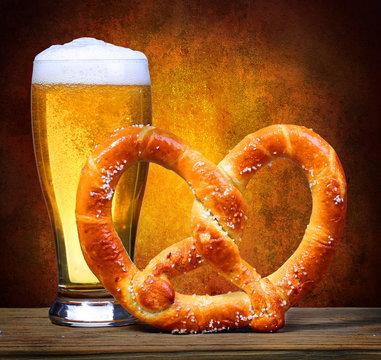 Beer Glass with German Pretzel over dark background