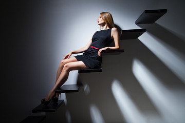 Pretty cheerful fashion model woman on ladder