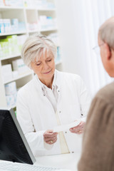 ältere apothekerin bedient einen kunden
