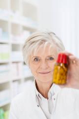 ältere apothekerin zeigt medikament