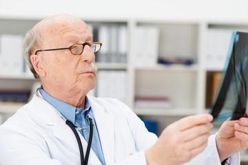 älterer arzt im krankenhaus prüft röntgenbild