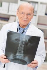 seriöser älterer arzt mit röntgenaufnahme