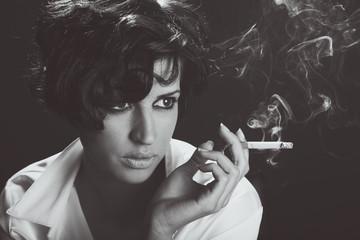 Elegant brunette woman smoking a cigarette on black background