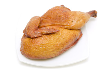roasted chicken on a plate on white background