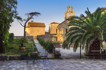 old town, square with stone buildings, an old church and a palm