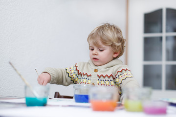 Cute toddler boy having fun indoor, painting with different pain