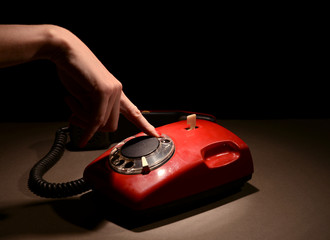 Red retro telephone,on dark background