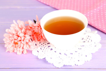 Pink chrysanthemums and cup of tea on wooden table