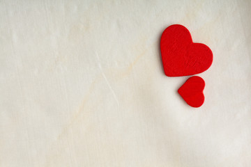 Red wooden decorative hearts on white cloth background.