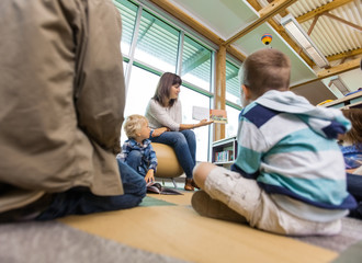 Teacher Reading To Students In Library