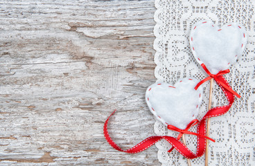 Valentine card with textile hearts on lacy cloth and old wood