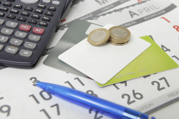 calculator, pen, coins and credit cards on a calendar
