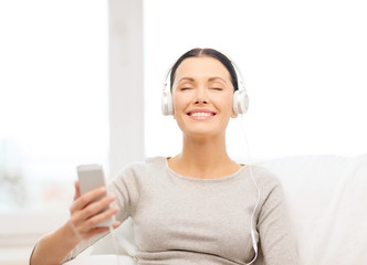 woman with smartphone and headphones at home