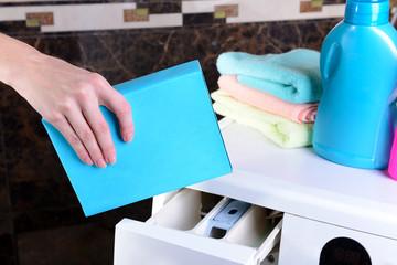 Female hands poured powder in washing machine close-up
