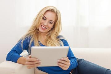 Beautiful blonde woman using digital tablet on sofa