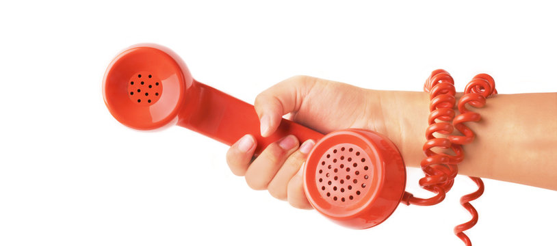 hand gripping telephone with cord wrapped around arm
