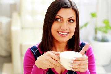 woman holding cup of coffee and looking up