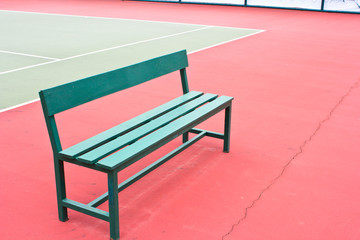 green chair in the tennis court.