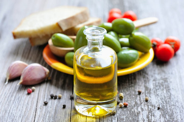 A bottle of oil, olives and spices on a wooden background