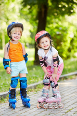 Smiling little boy and girl in protective equipments and rollers
