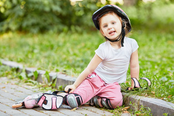 Little girl in protective equipment and rollers sits on curb