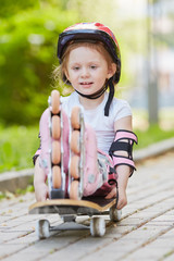 Little girl in protective equipment and rollers sits
