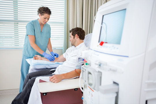 Nurse Injecting Patient For Renal Dialysis Treatment