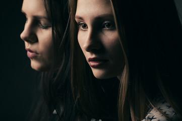 two girls studio portrait on dark background