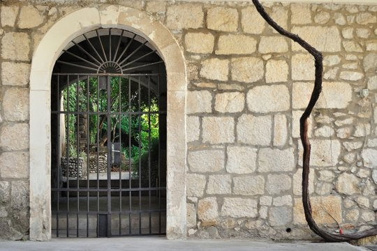 Medieval iron gate in ancient stone wall