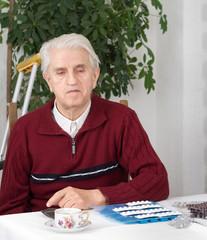 Portrait of senior man with pills