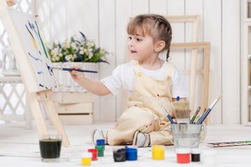 Little girl artist paints in his studio