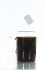 Sucre en morceaux qui tombe dans une tasse de café et éclabous