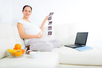 Beautiful pregnant woman with baby photos on sofa at home