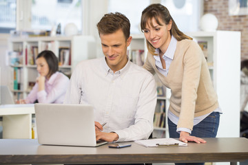 Cheerful business team working on computer in office