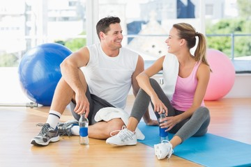 Young couple with water bottles chatting at gym