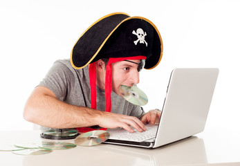 man in pirate hat downloading music on a laptop