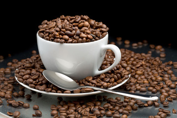 Cup and saucer full of coffee beans with a spoon