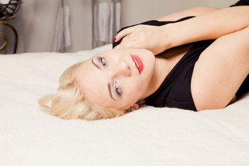 blonde posing lying on her back on light background