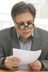 businessman wearing thick, circle glasses  reading at a document