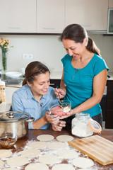 Two  women making  pies or  meat dumplings