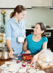 women making sweet dumplings  with berries