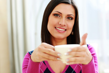 Middle-aged happy woman holding cup of coffee